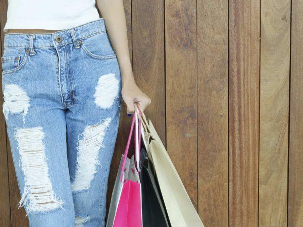 Frau mit Taillenjeans und Einkaufstaschen