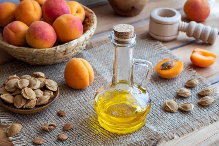 Flasche mit Öl neben Aprikosen