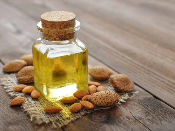 31137181 – almond oil in bottle on wooden background