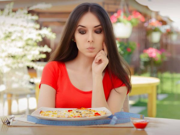 37428015 – young woman thinking about eating pizza on a diet