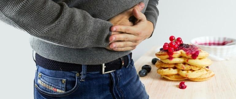 Mann hält sich Bauch vor Pfannkuchen