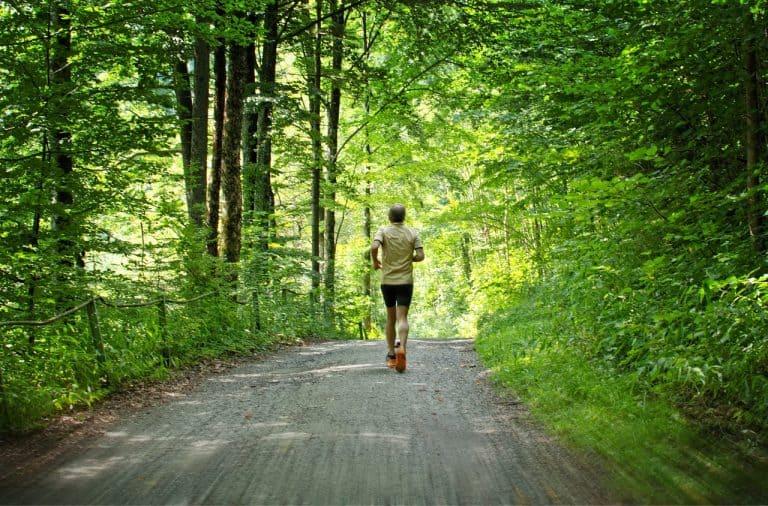 Mann joggt auf Waldweg