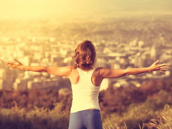Young woman spreading hands wide open with city on background. Freedom concept. Love and emotions, woman happiness. Toned image