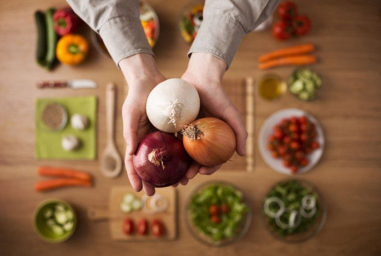 Eine Person hält Zwiebeln in der Hand. Auf dem Tisch darunter liegt Gemüse.