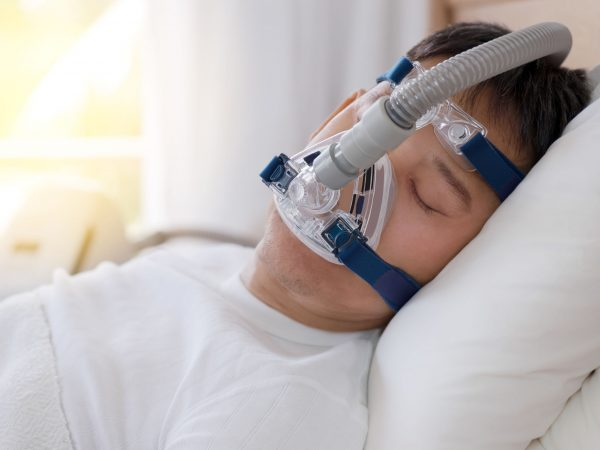 Sleep apnea therapy, Man sleeping in bed wearing CPAP mask. Healthy senior man sleeping deeply, happy on his back without snoring