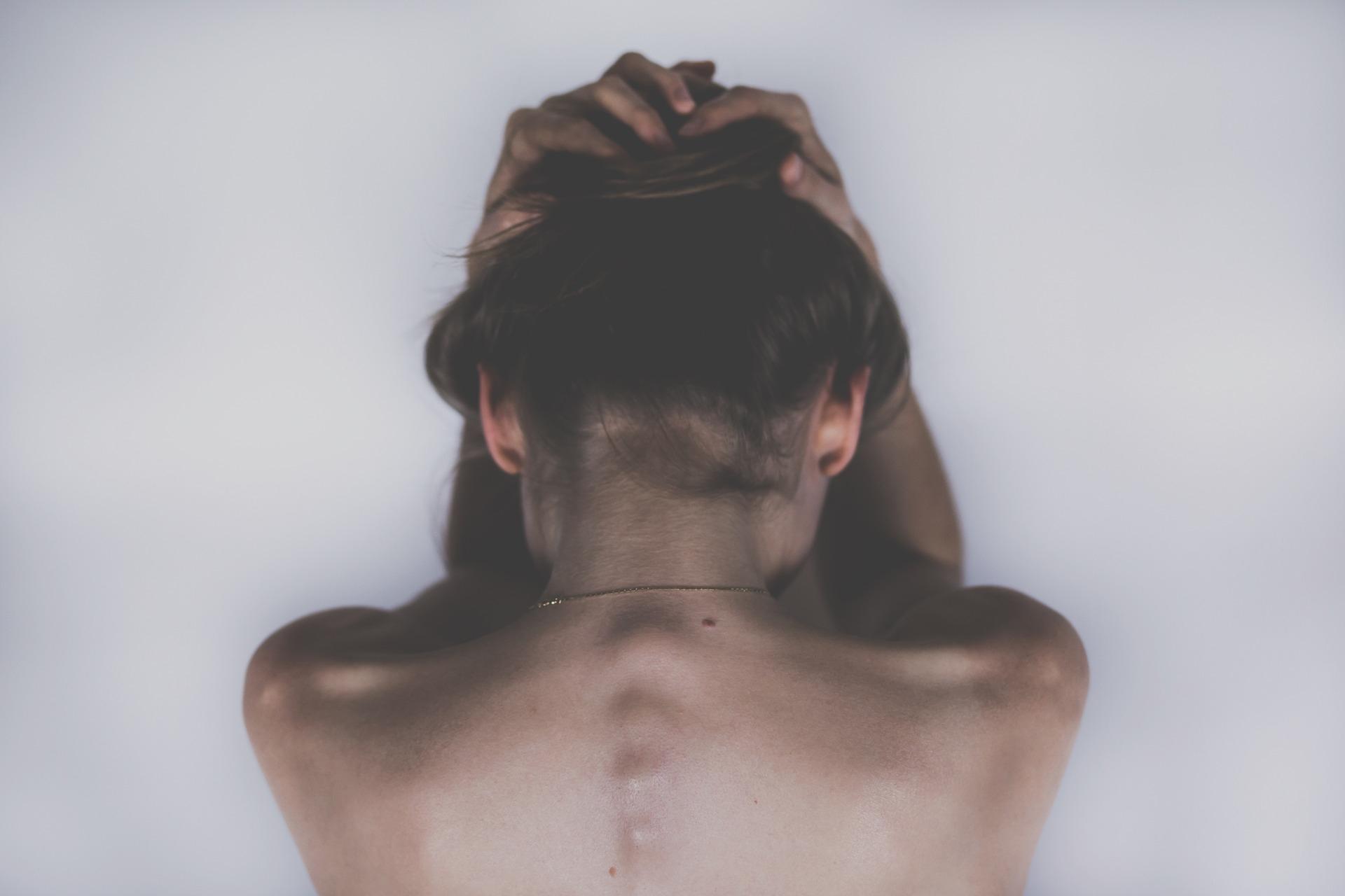Eine Frau steht mit dem Rücken zur Kamera vor einer weißen Wand.