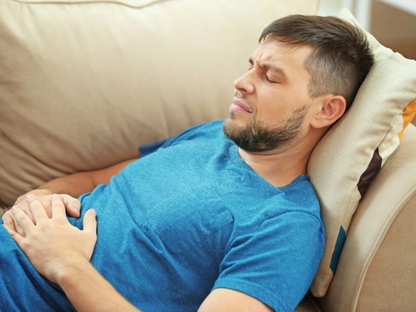 Handsome young man suffering from stomach ache while lying on sofa at home
