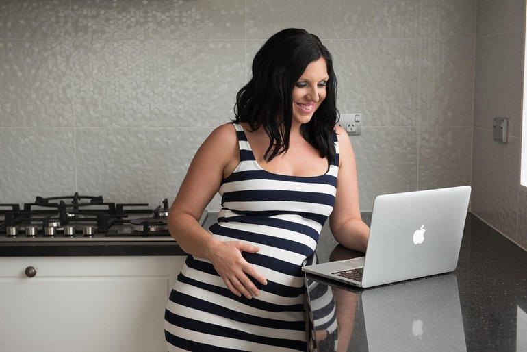 Schwangere Frau steht mit Laptop in Küche